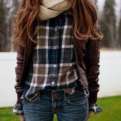 la chica lleva una camisa cafe y azul, la bufnda cafe, y los jeans azul.