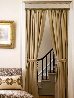 Curtains add glamour, increase privacy, buffer noise, and block drafts.  Here, the entrance from the dining area to the den is framed with thick, te