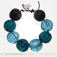 "Transparent teal tones ""seed pods""......5/8"" walnut shaped lamwporked beads. Organic, tribal, simply elegant. RWD 4/2015"