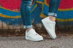 Frau mit blauen Jeans posiert vor Graffiti Wand mit weissen Sneakers