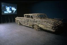 Drive In: Second Feature, 1982. Installation of tree branch sculpture and 16 mm film projection, color, with sound, 18 min., 53 sec., car: 60 × 80 × 216 inches (152.4 × 203.2 × 548.6 cm); screen: 159 × 108 × 70 inches (403.9 × 274.3 × 177.8 cm). Solomon R. Guggenheim Museum, New York Anonymous Gift, 2002 2002.13. © Roger Welch