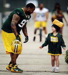 Johnny Jollytalks to a young fan as he walks toNFLfootball training camp Friday, July 26, 2013