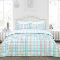 The Iona duvet set offers a contemporary check pattern in bright and beautiful tones. The duvet cover features a mix of pastel blue stripes, contrasted with pretty coral and yellow lines. The set is fully reversible, offering a white and blue check pattern.