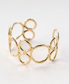 Rings of hammered brass coated in luxurious 14 karat gold loop around your wrist in this classic accessory.