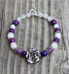 Purple Flower Memory Wire Cuff Bracelet $14.00 Here+is+another+beautiful+flower+bracelet+on+memory+wire.++The+beads+include+a+lilac,+black+and+white+polymer+flower+focal,+purple+tear+drop+crystals,+white+jade+and+purple+miracle+beads.++There+is+no+clasp,+but+one+can+be+added+for+free.++You+can+choose+from+a+toggle,+lobster+or+magnetic+clasp.