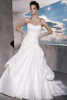 Brides: Demetrios - Sposabella. Taffeta A-line dress with a sweetheart neckline and lace-up back. Wrapped bodice features asymmetrical ruching and embellished embroidery. Side bustles finish A-line skirt.