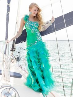 This gorgeous floor-length prom dress features a ruffled one-shoulder strap and fitted bodice. The top of this dress has been exquisitely adorned by peacock embellishments. These will definitely set you apart from the crowd as they create a luminous effect. A drop waist kick starts a long ruffled skirt that finishes in a slight train. -Bright green and blue dresses will draw attention to your best features, such as  green or blue eyes.