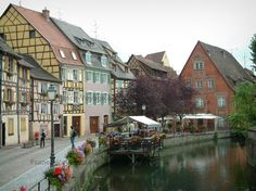 Colmar: Petite Venise (Little Venice): Lauch river, Poissonnerie quayside decorated with flowers, café terrace, trees and colourful half-timbered houses - France-Voyage.com