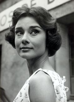 """The actress Audrey Hepburn photographed by Roger Viollet in front of the Studio de Boulogne, when Audrey was in Paris (France), for the filming of """"Love in the Afternoon"""", in September 1956. -Audrey was wearing a silk printed dress created by Hubert de Givenchy especially for her wardrobe in this film. Note: The Audrey's hairstyle, called Paris heart, was created and done by her favorite hairstylist, Alexandre de Paris."""