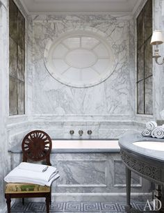 A Louis XVI side chair holds fresh towels.