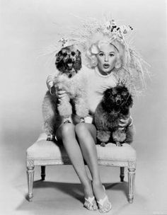 Mamie Van Doren and with her Poodle friends and just who is cuter???