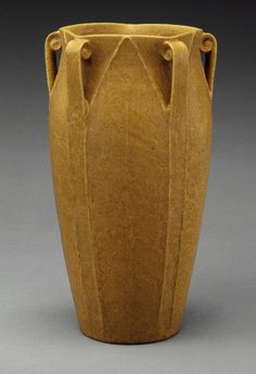 Vase, 1899–1910. Grueby Faience Company (American, 1894–ca. 1911). Boston, Massachusetts. Earthenware. Although Grueby pottery is traditionally known for the matte green glaze that became ubiquitous in Arts and Crafts potteries, this vase features an unusual mustard yellow glaze. At Grueby, potters crafted the pots and modelers—usually female—finished them. The design of the vase, which alternates between stylized flat leaf and thin elegant scroll, is attributed to George P. Kendrick.