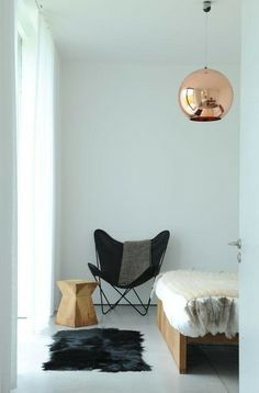 copper ball light + white wood floors + butterfly chair + fur