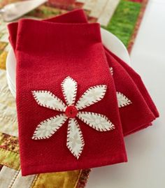 Give purchased napkins a holiday theme with a fused poinsettia and button and stitching embellishments.