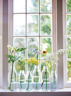 Dicas de como decorar sua casa de forma romântica e que tenha a sua cara –detalhes para esses vasos em garrafas de vidro com diferentes flores.