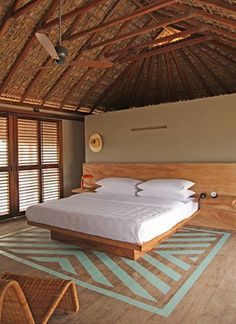 Bedroom of Hotel Escondido in Mexico with Blue-Green Painted Striped Floor and Thatched Palm Roof, Remodelista. Love this painted floor.