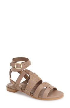 This chic gladiator-inspired flat sandal with a wraparound ankle strap and gleaming goldtone studs add an instant update to the warm-weather wardrobe.