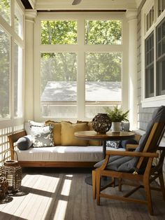 Back porch - Covered, screened patio with teak sofa, yellow pillows and lanterns.