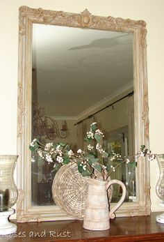 Roses and Rust: Mirror Magic. She took a plain mirror, got some resin decal pieces from the hardware store, glued them on, painted the frame and mirror and rubbed on a brownish paint to antique it. Nice