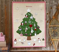"""A fun countdown to Christmas!  Each day until Christmas, this charming tree gets more and more beautiful as your child hangs another ornament. 39.5"""" wide x 51"""" high Expertly sewn of linen with polyester felt. Appliquéd details and embroidered stitching for a handcrafted look and feel. Tree is decorated with buttons for hanging an ornament each day."""