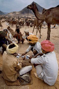 Steve McCurry, INDIA. Pushkar Camel Fair, Pushkar, Rajasthan, 2007. Men handle money at Pushkar Camel Fair.