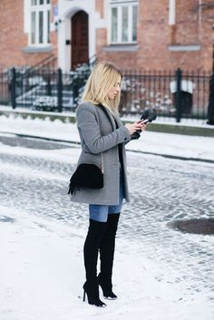 Winter outfit idea with grey jacket, black over the knee boots, jeans, and a black bag with tassel #winter #style #fashion