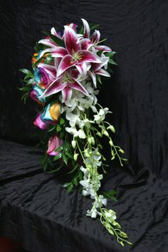 Stunning Stargazer Lilies, Rainbow Roses and Dendrobium Orchids in a trailing wedding bouquet.