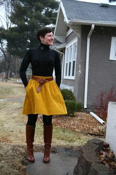 Black turtleneck, mustard skirt, black opaques, cognac belt and boots