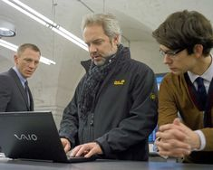 """On the set of """"Skyfall"""", 2012.  L to R: Daniel Craig, director Sam Mendes, Ben Whishaw.  By 2012, the James Bond movie franchise was in danger of disappearing forever when the Bond producers invited Mendes to direct the 23rd installment.  His emphasis on the characterization (introducing Whishaw as Q, Naomie Harris as Moneypenny, Ralph Fiennes as M's replacement, and a memorable villain played by Javier Bardem) would boost the production into new territory. Ben Whishaw, Ben Affleck, Sam Mendes, Javier Bardem, Z Cam, Ralph Fiennes, James Bond Movies, Mark Wahlberg, Skyfall"""