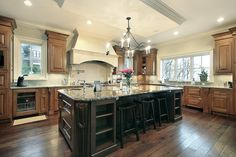 Massive square shaped kitchen with extensive counter space and enormous dark wood island with dark granite top.