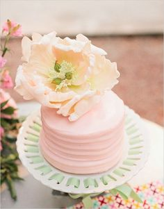 Mini pink cake with large floral topper.