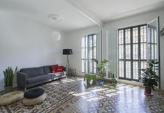 La zona giorno open space dell'appartamento The VVall, a Barcellona, con balconea sulla strada. L'arredo è eclettico: riconosciamo i futon in treccia di paglia di Ikea, mentre il divano grigio è un modello di BoConcept. Lampada Tripode G5 by Santa & Cole