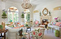 Large living room with creamy walls and couches and accents of greens, pinks and blues - very Palm Beach -Mario Buatta