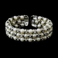 """Lustrous and radiant, this stylish bracelet features three rows of shining glass pearls and glittering rhinestones in an alternating pattern set in gorgeous antique silver. This striking bracelet is perfect for the bride, bridesmaids or the prom queen.   Size: 2.5"""" diameter with an 8"""" circumference and 0.75"""" tall, adjusts to fit most wrists"""