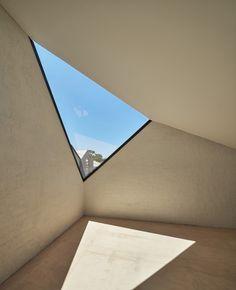 brique de parement intérieur en blanc neige et fenêtre triangulaire