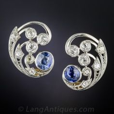 Just over 1 inch by 3/4 inch, chic and striking platinum ear clips hailing from the 1930s. Flowing kinetic swirls, studded with almost 3 carats of bright white old mine-cut diamonds, culminate in a pair of vivid cornflower blue natural, no-heat Ceylon sapphires, together weighing 4 carats. Stunning and impressive vintage ear baubles.