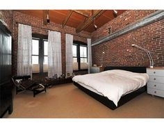 This luxury Boston Seaport penthouse loft bedroom has beautiful and stylish red brick exposed walls.