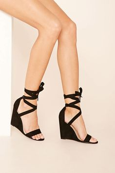 A pair of faux suede wedges with a lace-up ankle and a single toe strap.