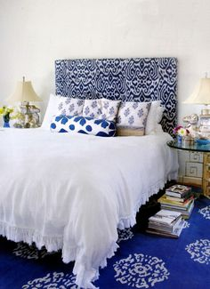 Blue Luce Ikat Fabric upholstered headboard, Casper Pillows, Blue Fauve Suzani bolster, and Blue Mandala Tibetan Carpet in Madeline Weinrib's Hamptons Home - via Hamptons Cottages & Gardens