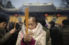 A woman burns joss sticks while praying at Longhua Temple on the first day of the Lunar New Year in Shanghai, China on Sunday, Feb. 10, 2013. (AP Photo/Eugene Hoshiko) ▼11Feb2013AP|AP PHOTOS: Celebrating Lunar New Year around world http://bigstory.ap.org/article/celebrating-lunar-new-year-china-around-world