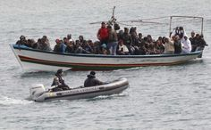 Migrants from North Africa arrive in 2011 escorted by Italian financial police at the southern Italian island of Lampedusa. Pope Francis will visit the tiny island July 8 to greet refugees and immigrants, pray for those who have lost their lives at sea and call for greater solidarity. (CNS photo/Stefano Rellandini, Reuters)