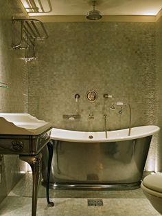Large soaking tub with ceiling mounted showerhead, tiled floors and walls - Max Rollitt in London