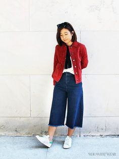 A white t-shirt is worn with a skinny scarf, suede jacket, denim culottes, and white sneakers
