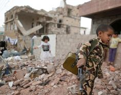 A boy carries a toy gun next to destroyed houses during a vigil marking one year since a Saudi-led air strike on a residential area in Sanaa, Yemen. | (REUTERS/Khaled Abdullah)