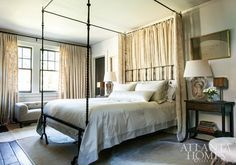 In this master bedroom a 17th-century reproduction Italian iron bed by Gregorius Pineo takes center stage. The white-on-white crewel fabric is by Old World Weavers. The lamps were designed from late-19th-century oak carvings. Design by Susan Ferrier, McAlpine, Booth & Ferrier Interiors. Photo by Erica George Dines. From www.atlantahomesmag.com.