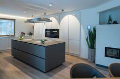 Graue Küche: Kochinsel in dunklem Grau als Kontrast zu weißen Küchenschränken in Hochglanz