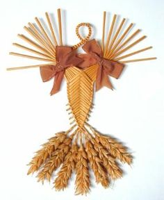This corn dolly is of the type known as a 'Welsh border fan'. It is made of wheat and decorated with brown ribbons.  (MERL/87/39)