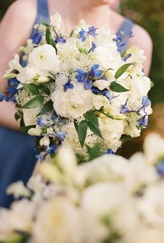 The bridesmaids will carry round clutch bouquets of white hydrangeas, ivory spray roses and hints of blue delphinium wrapped in light blue ribbon with the stems showing (no greenery though!).
