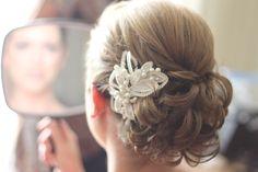 Classic low bun updo with  decorative clip www.weddingsbycrystal.com