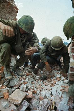 U.S. Marines dig with their hands through brick rubble burying PFC Thomas A. Zwetow who was standing on a tower of the citadel when it was hit by communist artillery. He was trapped for six hours before Marines returned to the site and saw his hand sticking out from under the stones. It took twenty minutes to extricate him.